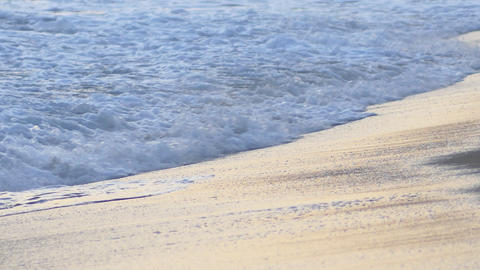 Rough, colored ocean waves wash over golden sandy beach at sunset time. Footage