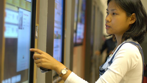 Asian Woman using self-service tickets machine in cinema Footage