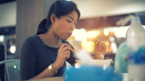 Young Asian Lady eating noodle soup in food court toned video Footage