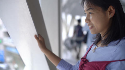 Young Asian woman is looking at the city from window Footage