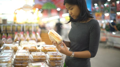 Young Asian woman is choosing bakery products in supermarket Footage