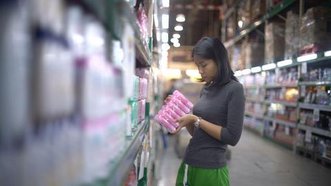 Asian girl is choosing household chemicals in supermarket Footage