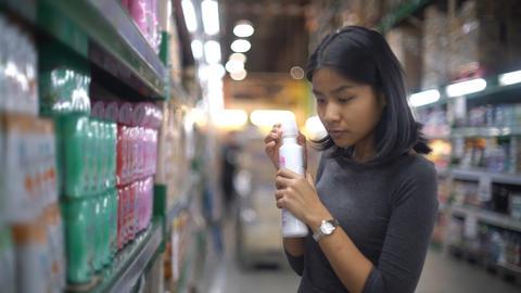 Asian girl smells shower gel in supermarket Live Action