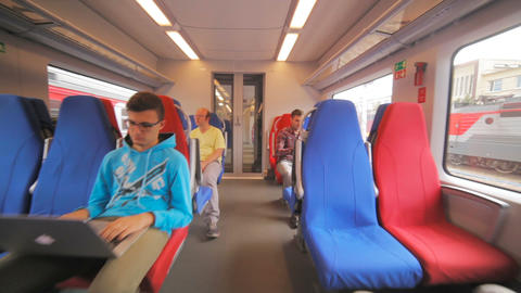 young men travel in comfort chairs on electric train Footage