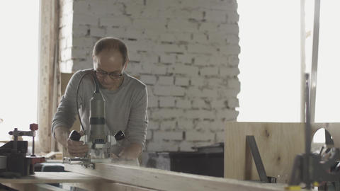 Locksmith in glasses cutting wooden board by plunge router. Treatment. Sawdust Footage