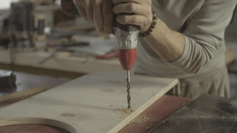 Professional woodworker perforate holes in polished wooden board by drill Live Action