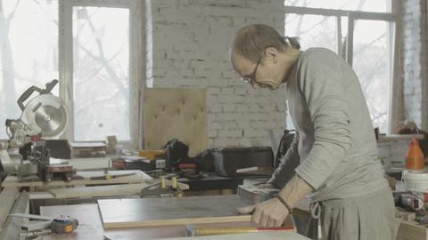 Professional woodworker polish edge of wooden board by belt sander machine Live Action