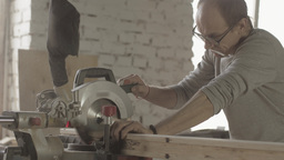 Professional carpenter cut long wooden board by circular saw. Furniture Footage