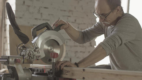 Professional woodworker cut long wooden board by circular saw. Furniture Live Action