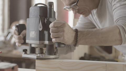 Woodworker treats long wooden board on edge by plunge router. Manufacturer Live Action