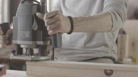 Woodworker treats edge prepared wooden board by polishing machine. Manufacturer Live Action
