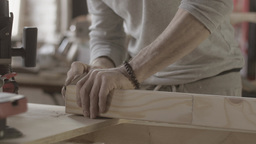 Woodworker polish edge of long wooden board by special sponge. Manufacturer Live Action