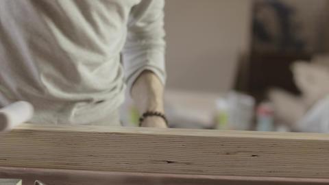 Woodworker dye long wooden board by varnish. Roller. Manufacturer. Treatment Live Action