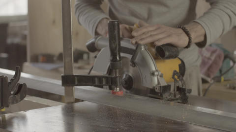 Woodworker cut wooden board on straight line of metal balk. Circular saw Live Action