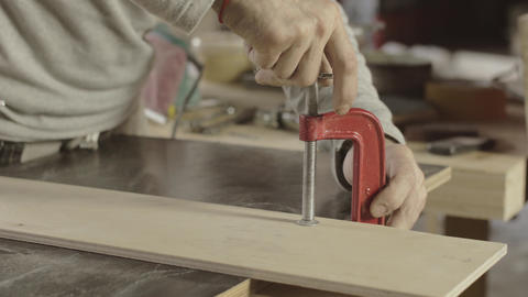 Professional carpenter fixing one wooden board on another. Making furniture Footage