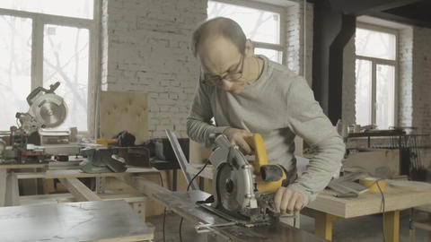 Professional carpenter fixing circular saw on of wooden board on work table Footage
