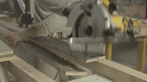 Carpenter cut wooden board on two parts by circular saw. Woodworker Live Action