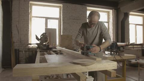Aged woodworker attentively treat wooden board by belt sander. Manufacturer Live Action