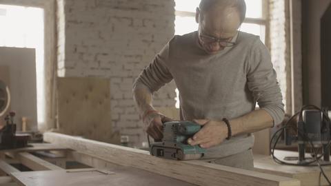 Aged woodworker careful treat wooden board by belt sander. Manufacturer Live Action