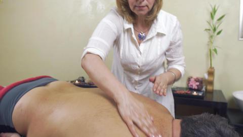 Masseuse make therapeutic massage to fat man. Rubdown of back. Medium shot Live Action