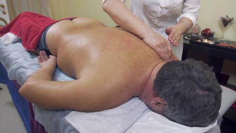 Masseuse press shoulders, backbone of fat man. Therapeutic massage. Medium shot Live Action
