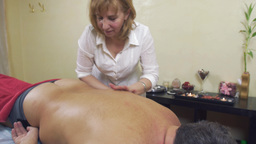 Masseuse specialist rubdown left side of back to adult fat man. Medium shot Live Action