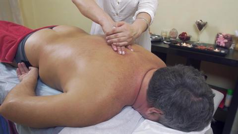 Masseuse hands press backbone of adult fat man. Remedial massage. Medium shot Live Action