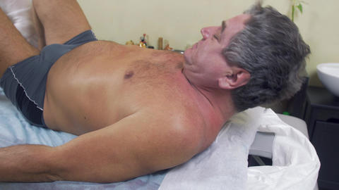 Adult fat man turn over and lie on back. Therapeutic massage. Medium shot Live Action