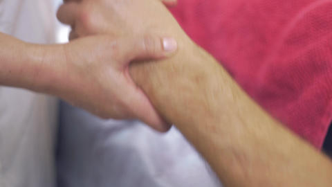 Close up of masseuse hands make professional massage of hand hand to adult man Live Action