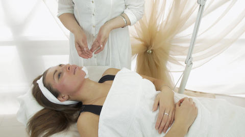 Professional female cosmetologist waxing girl chin in beauty saloon. Medium shot Live Action