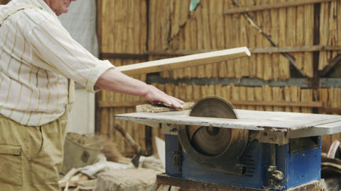Senior man sawing wood on the machine with a circular saw Footage