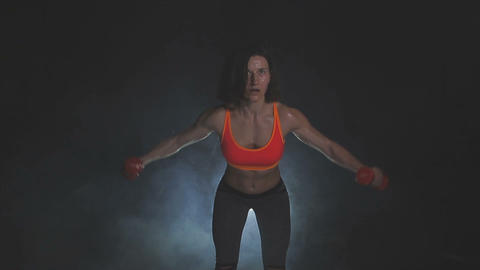 Beautiful fitness woman with lifting dumbbells . Sporty girl showing her well Footage