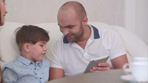 Young father showing something on the tablet to his wife and sons Footage