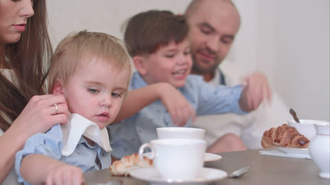 Happy young family of four having tea at restaurant or cafe or home Footage