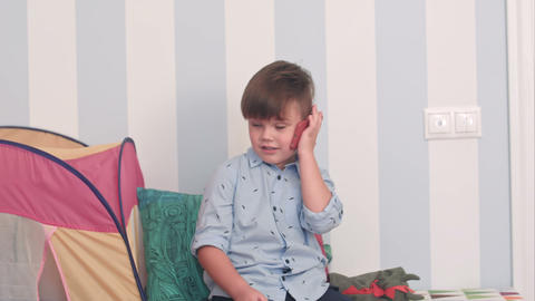 Smiling little boy talking on mobile phone in his room Footage