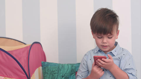 Excited little boy reading a message on his phone Footage