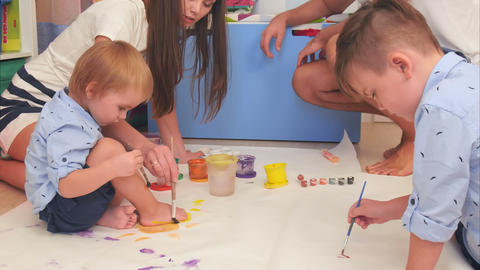 Two little brothers and their parents painting with watercolors Footage