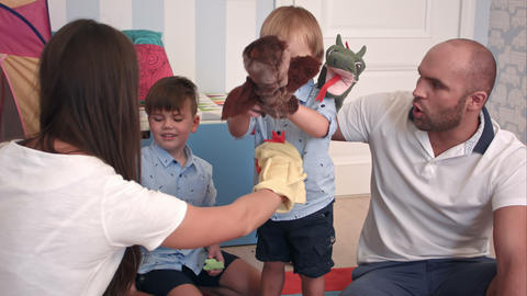 Father and mother playing animal hand puppets with their boys Footage