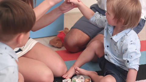 Young parents teaching their little sons how to play with finger puppets Footage