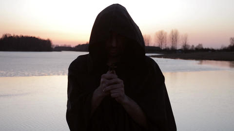 A monk prays on the shore of the lake, holding a cross Live Action