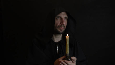 Bearded monk reads a prayer by candlelight, the flame of a candle sways 9 Live Action