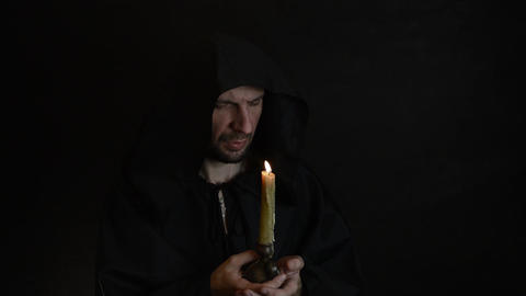 A bearded monk reads a prayer by candlelight, the flame of a candle sways 2 Live Action