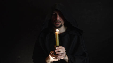 A bearded monk reads a prayer by candlelight, the flame of a candle sways 6 Live Action