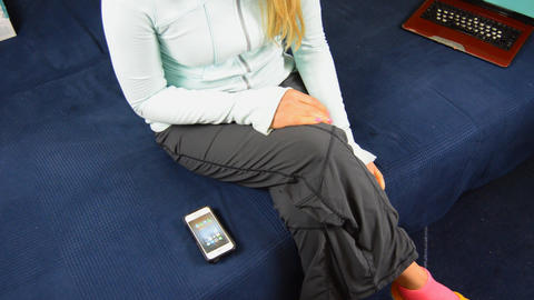 Woman Checks Apps on Smartphone On Couch GIF