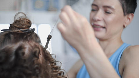 Hairdresser makes curly afro hairstyle for woman by hot curling hair, process of Footage