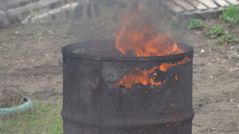 Fire burns in an old rusty barrel Footage