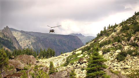 Rescue helicopter fly ower a high rocky mountain Footage