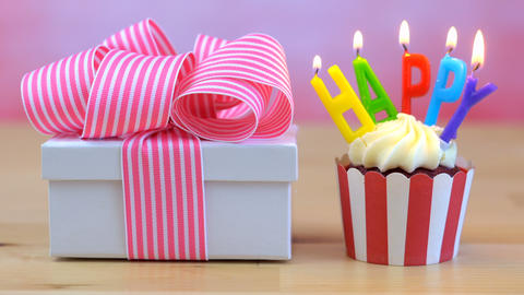4k Happy Birthday cupcake with colorful candles with small gift wrapped in pink Footage