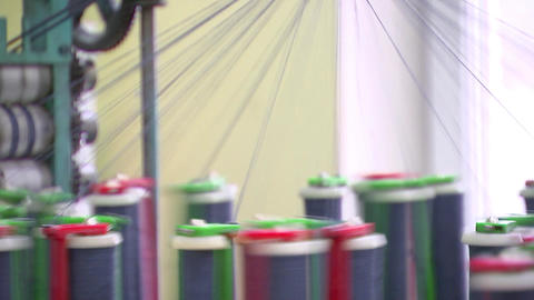 Garment manufacturing, with multi-colored coils coming off the thread Live Action