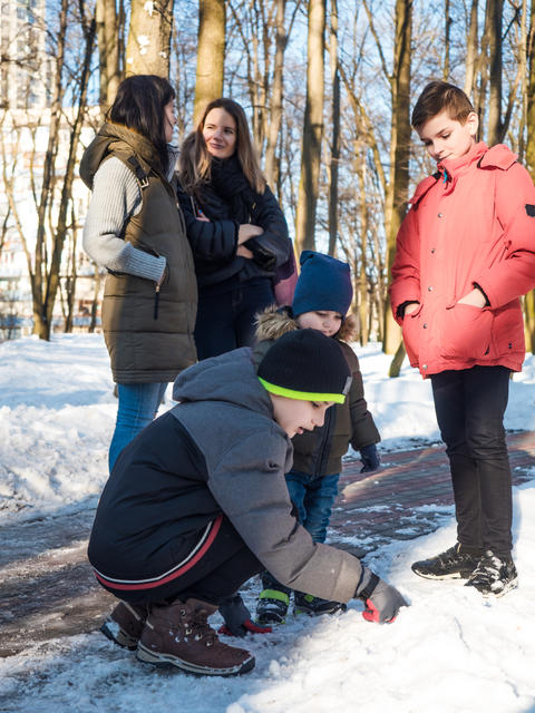 Two mothers talking during their children play with snow in winter park Photo